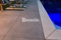 Antique White and Slate Gray Bomanite Revealed decorative concrete were installed here with a scattering of mirror glass, adding sparkle and sophistication to the durable decking surface.