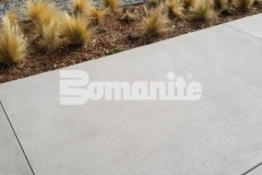 The Bomanite Sandscape Refined Exposed Aggregate System was utilized here and incorporates white color hardener paired with locally sourced aggregates, mirror glass, and distinctive saw cuts to enhance the nautical themed design at the 50 Fifty DTC office complex.