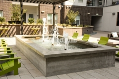 The increasingly popular technique of board-forming was used here to imprint wood grain onto concrete, creating a stunning water feature with a visually softened surface that is the perfect addition to this gathering space at the COLAB Co-Housing Development.