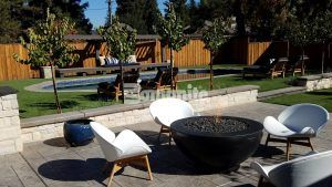 Firepit seating area with a view of the pool at a private residence in Fresno, CA, featuring decorative concrete using Bomanite Imprint Systems with English Sidewalk Slate Pattern installed by Heritage Bomanite.