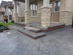 Angled view of the porch and steps with part of driveway in the foreground highlighting Bomanite Imprint Systems decorative concrete using Yorkshire Stone Pattern with Bomanite Shale Gray Color Hardener installed at a residence in Burlington, Ontario, by Bomanite Toronto located in Vaughn, Ontario near Toronto Canada.