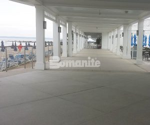 Covered walkway long view between beach and umbrella tabled eating area showcasing Bomanite Revealed Exposed Aggregate Systems decorative concrete installed at Westchester CC Beach Club by Beyond Concrete of Keyport, NJ.