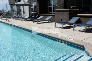 Pool view of featuring Bomanite Sandscape Texture decorative concrete at CoLab Student Living Housing Community in Denver installed by Colorado Hardscapes using Bomanite Exposed Aggregate Systems, Bomanite Toppings Systems and Board Formed Concrete.