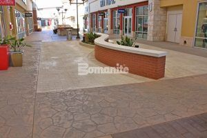 S curved wall in the center of a walkway at the Tanger Outlets Fort Worth Location featuring Bomanite Imprint Systems installed by Texas Bomanite with design by Adams & Associates.