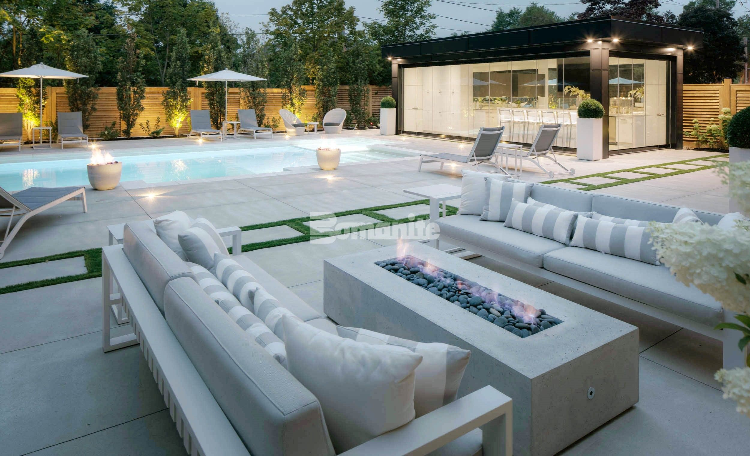 Firepit seating area of an elegant backyard pool deck using the Bomanite Sandscape Refined Exposed Aggregate System with bands of grass installed by Bomanite Toronto in Canada.