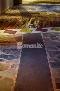 Pathway of Bomanite Sandscape Texture decorative concrete between the stonework and the Bomanite Revealed Glass Aggregate flooring at Choctaw Cultural Center in Durant, OK, installed by Bomanite of Tulsa.